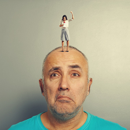 sad man with small aggressive woman on his head over grey background photo