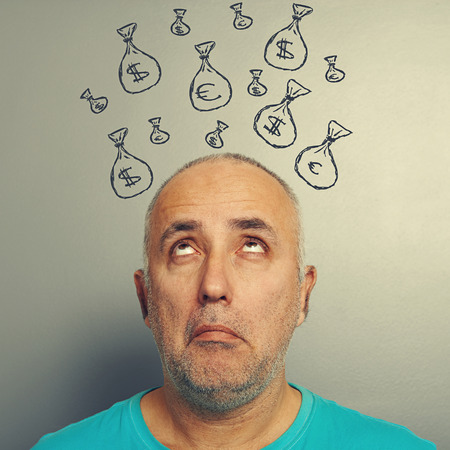 amazed senior man looking up at bags with money photo