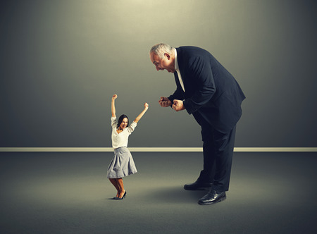 mad boss screaming at small joyful woman over dark background photo