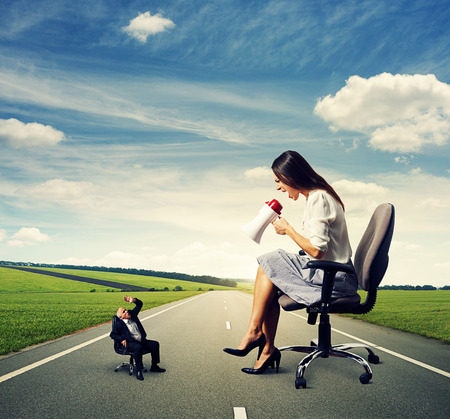discontented: discontented big woman screaming at small frightened senior man on the road Stock Photo