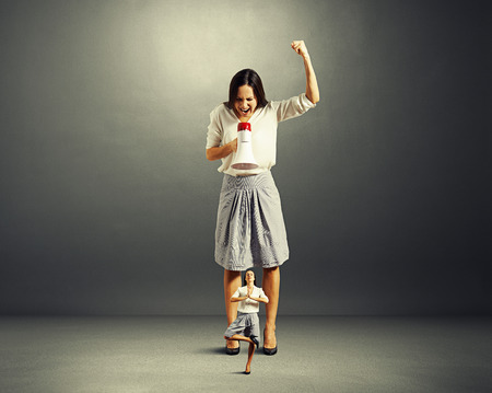 discontented: discontented businesswoman screaming at small yoga woman over dark background Stock Photo