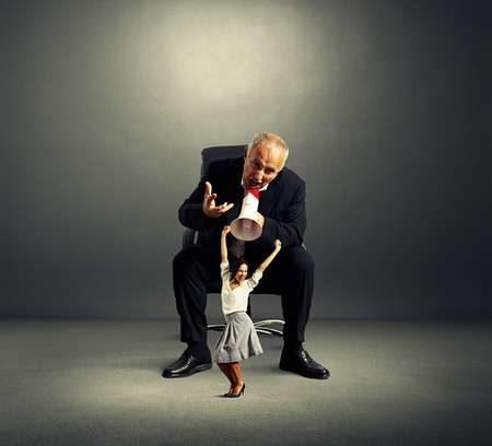 displeased businessman: displeased businessman and joyful businesswoman over dark background