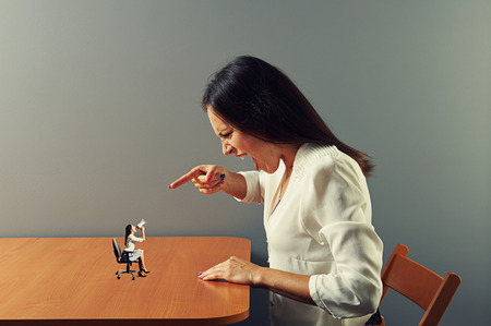 big women: displeased woman screaming at small woman on the table
