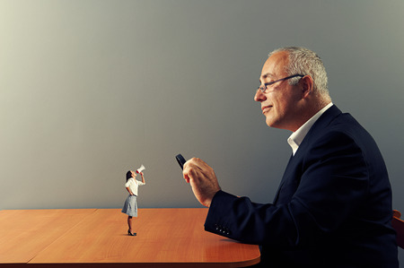 smiley businessman with loupe and small businesswoman with megaphone photo