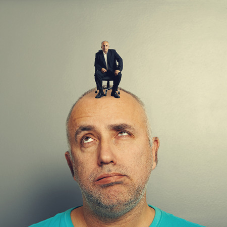weary senior man with small businessman on his head photo