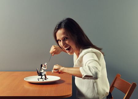 evil woman ready to eat small woman with megaphone on the plate photo