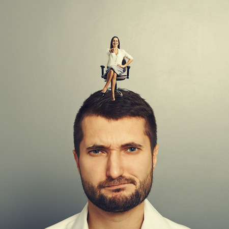 small smiley woman sitting on the displeased man and pointing photo