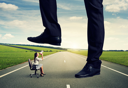 downtrodden: displeased woman screaming at big man on the road Stock Photo