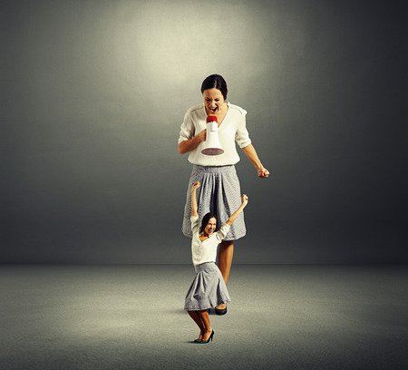 happy woman and angry big woman over dark background photo