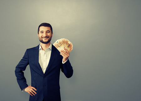 riches adult: handsome businessman holding paper money and smiling over grey background Stock Photo