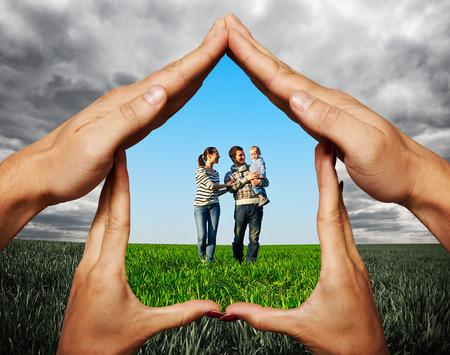 handen bescherming van jonge familie op het veld