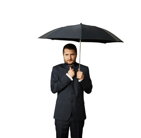 displeased: displeased businessman under black umbrella. isolated on white background