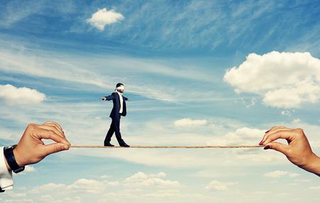 zakenman met gesloten ogen balanceren op het touw Stockfoto