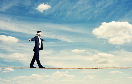 man met de blinddoek lopen op het touw over de blauwe hemel Stockfoto