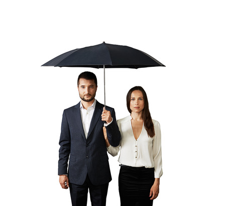 serious businessman: serious couple under umbrella. isolated on white background