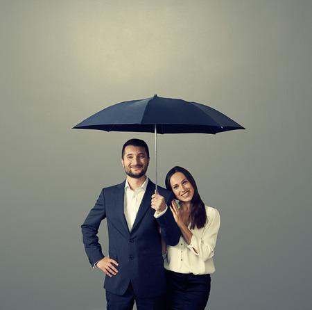 smiley couple under umbrella over dark background photo