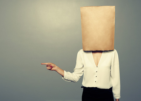 hiding face: woman with paper bag on the head pointing at something over dark background
