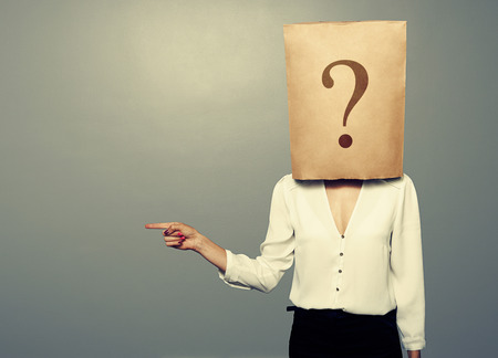 businesswoman with paper bag pointing at something over dark background