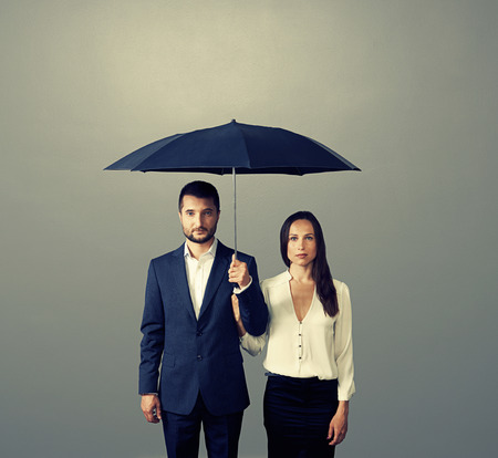 serious couple under umbrella