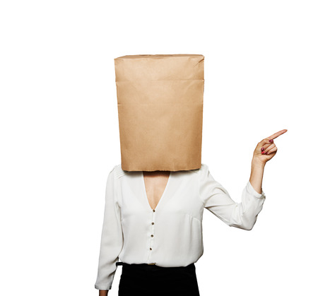 businesswoman with paper bag on the head pointing at something.  photo