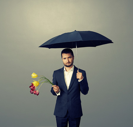 sad man with faded flowers standing under umbrella over dark background Stock Photo