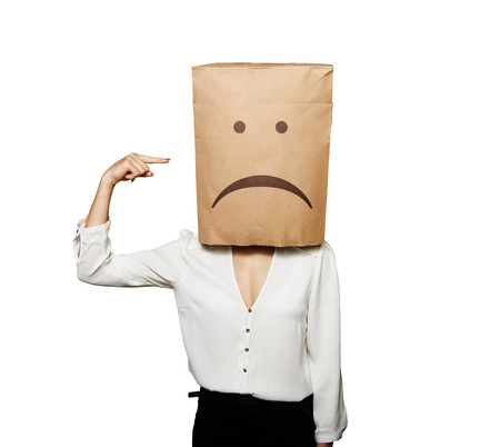 depressed woman pointing at paper bag on the head over white background