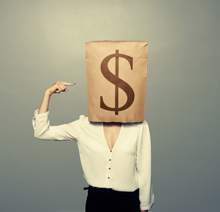 businesswoman with paper bag on her head pointing at dollar background photo