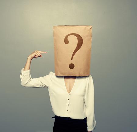 mujer de negocios con la bolsa de papel que señala en la pregunta sobre fondo oscuro