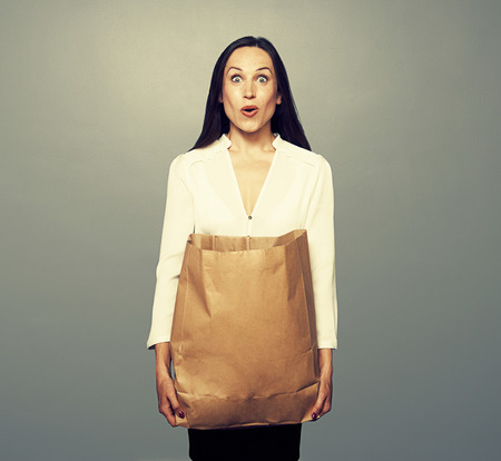 amazed young woman holding paper bag over dark background Stock Photo - 29018697