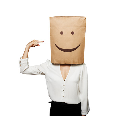 woman pointing at paper bag on the head over white background photo