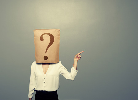 shopping questions: woman with paper bag pointing at something over dark background