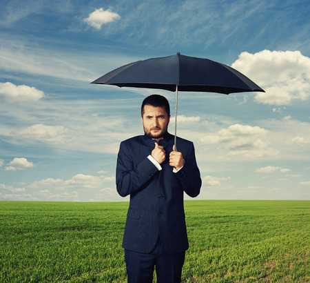 weather protection: displeased businessman under black umbrella at outdoor