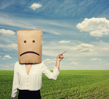 despaired: sad businesswoman pointing at something over green field