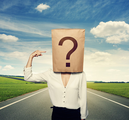 businesswoman with paper bag on the head pointing at question photo