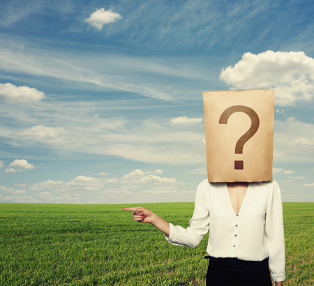 businesswoman with big question pointing at copyspace photo