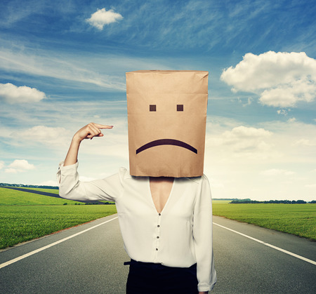 despaired: concept photo of bad mood. woman with paper bag on the head Stock Photo