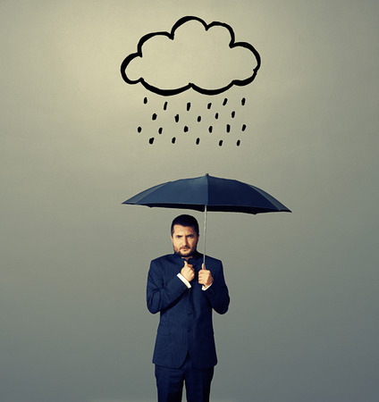 displeased businessman with umbrella standing under drawing storm cloud over dark background photo