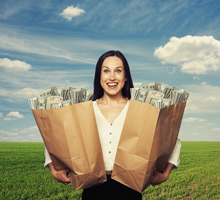woman holding money: excited young woman holding bag with money over blue sky and green field Stock Photo