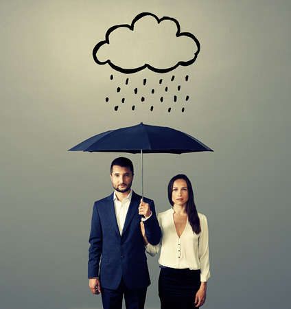 serious couple with black umbrella standing under drawing storm cloud. photo over grey background photo