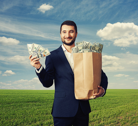 smiley handsome businessman holding paper bag with money and showing dollars.  photo over blue sky and green field Stock Photo - 29619614