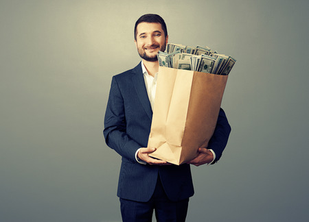 handsome smiley businessman holding paper bag with money over grey background Stock Photo - 29619617