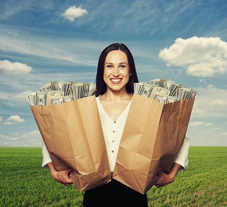 erfolgreiche frau: smiley erfolgreiche Frau h�lt zwei T�ten mit Geld �ber blauen Himmel und gr�nen Bereich