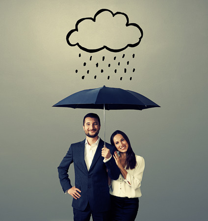 smiley young couple with black umbrella standing under drawing storm cloud. photo over grey background Stock Photo - 29619625