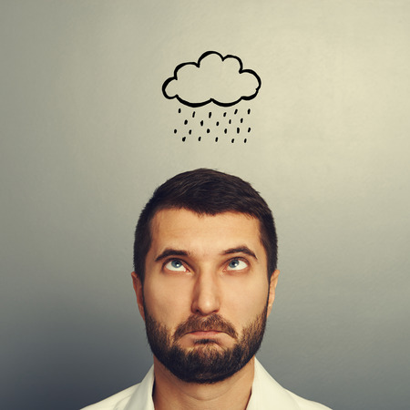 discredit: portrait of stressed man with drawing storm cloud over grey background Stock Photo