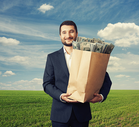 successful and handsome businessman holding paper bag with money and smiling over blue sky and green field Stock Photo - 29619628