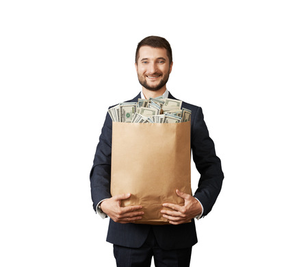 successful businessman holding paper bag with money and smiling. photo in studio over white background Stock Photo - 29619630