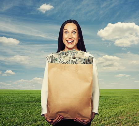 erfolgreiche frau: aufgeregt, erfolgreiche Frau h�lt Tasche mit Geld �ber blauen Himmel und gr�nen Bereich