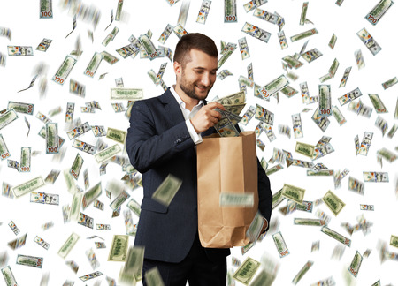 money rain: smiley young businessman standing under money rain and putting dollars in the paper bag