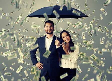 falling in love: smiley successful couple with umbrella standing under money rain Stock Photo