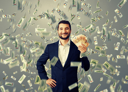 rich: happy smiley businessman standing under money rain and holding euro Stock Photo